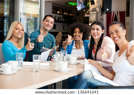 Group of  success students in cafe showing thumbs up - stock photo