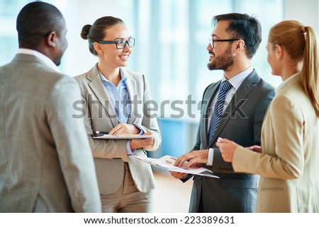 Group of successful business partners discussing plans or ideas at meeting - stock photo