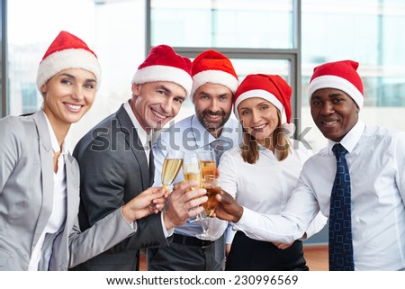 Group of successful business partners in Santa caps toasting with champagne and looking at camera - stock photo