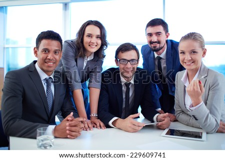 Group of successful business partners looking at camera at meeting - stock photo