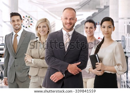 Group of successful business people at bright office, standing, smiling, happy, looking at camera. Suit.