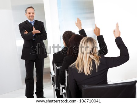 Group of successful business people at the lecture asking questions - stock photo