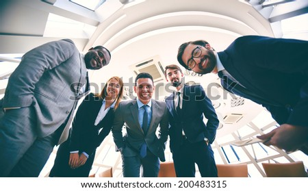 Group of successful business people in suits looking at camera - stock photo