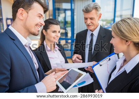 Group of successful business people in suits on business meeting. Office background.