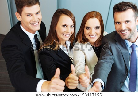 Group of successful business people showing thumbs up - stock photo
