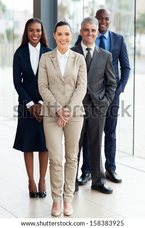group of successful businesspeople standing in office - stock photo