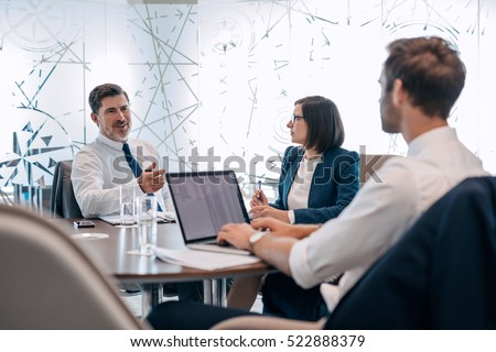 Group of successful businesspeople talking together while working around a table in an office boardroom