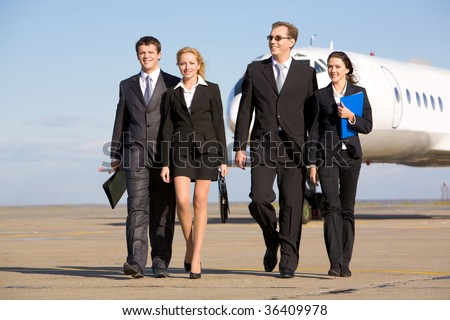 Group of successful people walking on the background of the airplane - stock photo