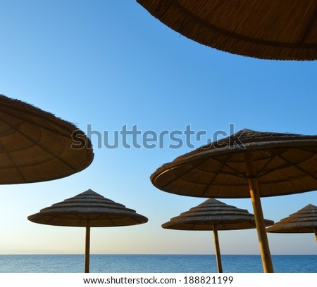 Group of sunshades against the sky blue - stock photo