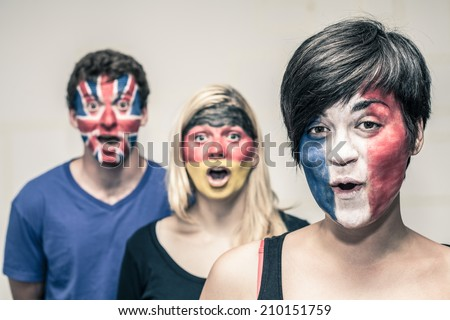 Group of surprised happy people with painted flags on their faces. - stock photo