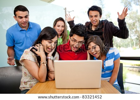 Group of surprised students at the university with a computer - stock photo