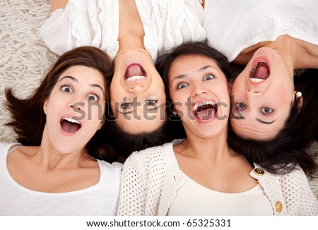 Group of surprised women lying on the floor making faces - stock photo
