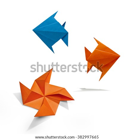 Group of swimming fishes in Origami, there is a path for each bird. - stock photo