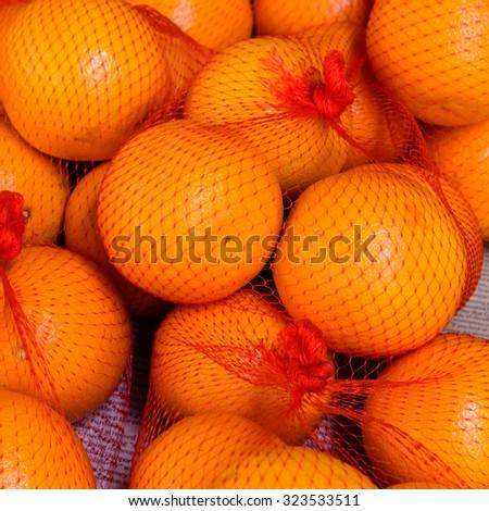 Group of tangerines (mandarines) in net bag on display at Bugis Village wet market in Singapore - stock photo