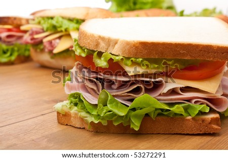 group of tasty sandwiches on a wooden table - stock photo