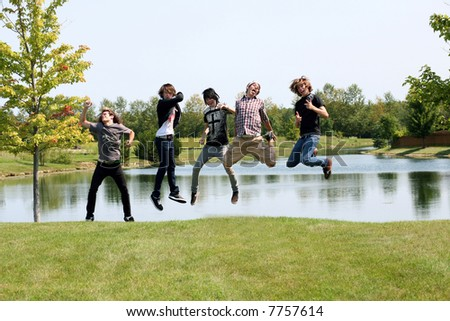 group of teen boys jumping by a lake - stock photo
