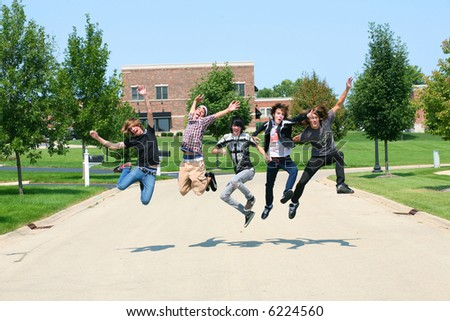group of teen boys jumping in the street