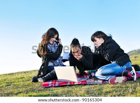 group of teen girl woman outdoor have fun and study homework on laptop computer - stock photo