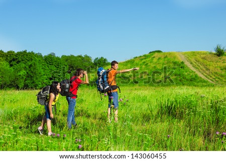Group of teenage backpackers observing the area - stock photo