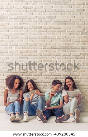 Group of teenage boy and girls is using gadgets, talking and smiling, sitting against white brick wall - stock photo