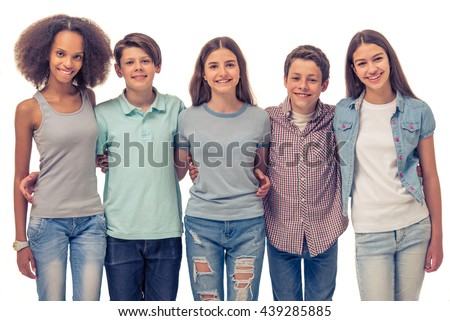 Group of teenage boys and girls is hugging, looking at camera and smiling, standing in row, isolated on white, - stock photo