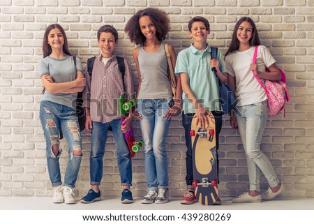Group of teenage boys and girls with school backpacks and skateboards is looking at camera and smiling, standing against white brick wall - stock photo
