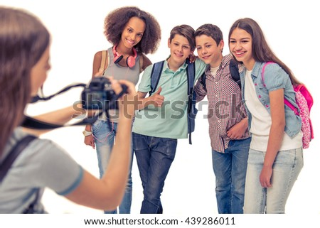 Group of teenage boys and girls with school backpacks is posing and smiling while their friend is taking photo - stock photo