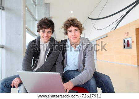 Group of teenage boys at school with laptop computer - stock photo
