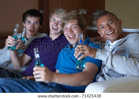 Group Of Teenage Boys Sitting On Sofa At Home Watching Drinking Alcohol