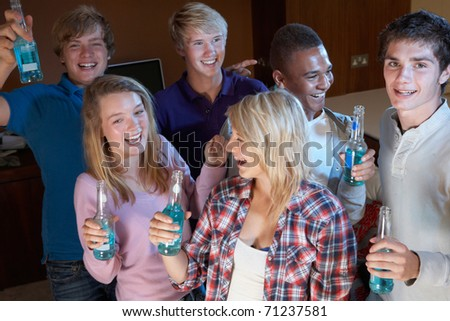 Group Of Teenage Friends Dancing And Drinking Alcohol - stock photo