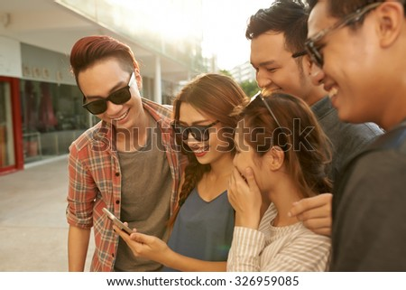 Group of teenage friends enjoying photos on smartphone