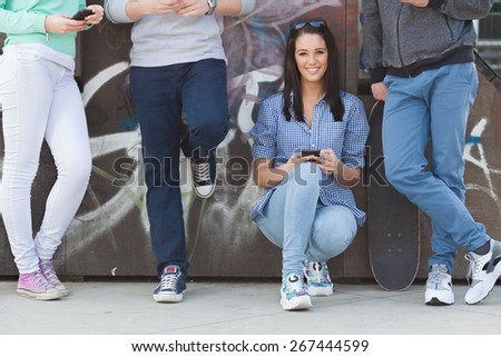 Group of teenage friends hanging out in a skatepark. Portrait of pretty girl holding her mobile phone and smiling - stock photo