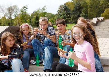 Group of teenage friends having fast food - stock photo