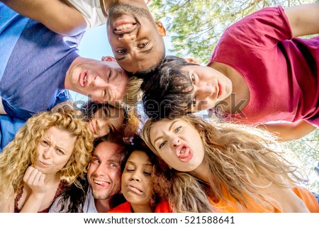 group of teenage friends making funny faces taking picture looking down at camera in a circle - concept of carefree funny young people having fun together outdoors