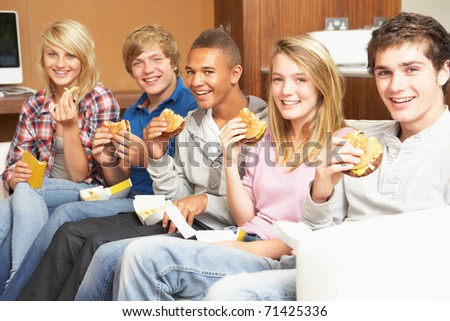 Group Of Teenage Friends Sitting On Sofa At Home Eating Fast Food - stock photo
