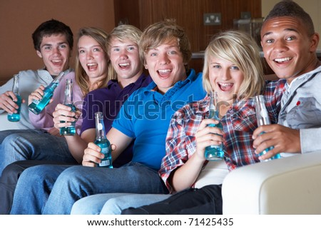 Group Of Teenage Friends Sitting On Sofa At Home Watching Drinking Alcohol - stock photo