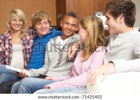 Group Of Teenage Friends Sitting On Sofa At Home Watching TV - stock photo