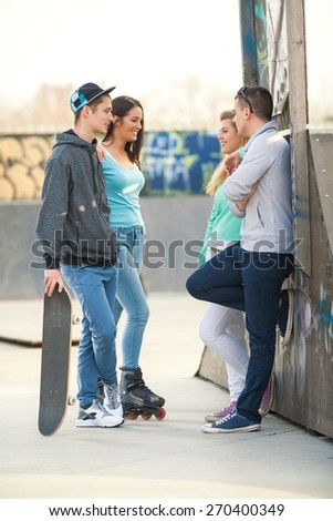 Group of teenage friends standing and talking in a skate park - stock photo