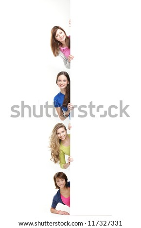Group of teenage girls with a giant, blank, white billboard - stock photo