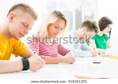 Group of teenage students at the exam in the auditorium - stock photo