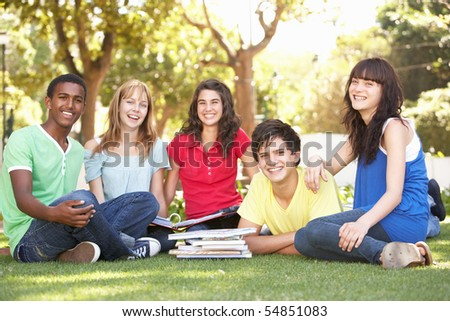 Group Of Teenage Students Chatting Together In Park - stock photo