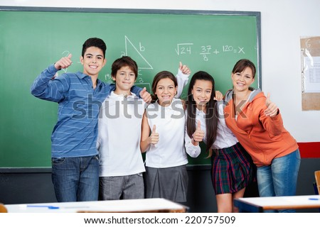 Group of teenage students gesturing thumbs up together in classroom - stock photo