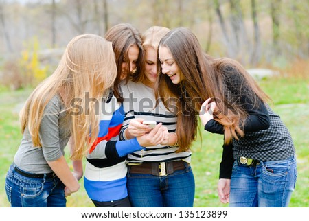 Group Of Teenage Students outdoors Using Mobile Phone - stock photo