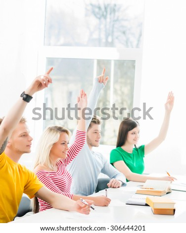 Group of teenage students raising hands  - stock photo