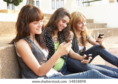 Group Of Teenage Students Sitting Outside On College Steps Using Mobile Phone - stock photo