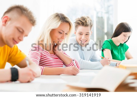 Group of teenage students studying at the lesson in the classroom