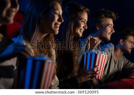 Group of teenager friends at the cinema watching a movie together and eating popcorn, entertainment and enjoyment concept - stock photo