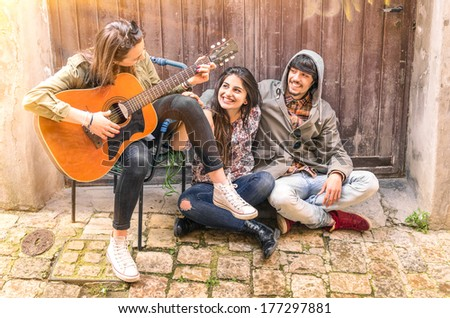 Group of teenager friends having fun playing Guitar - stock photo