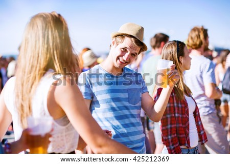 Group of teenagers at summer music festival, sunny day. Young teens at summer music festival. Funny group of young girls and boys at music festival. Crazy teens with beer at summer festival.