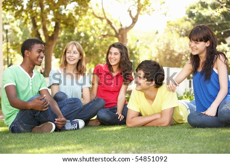 Group Of Teenagers Chatting Together In Park - stock photo